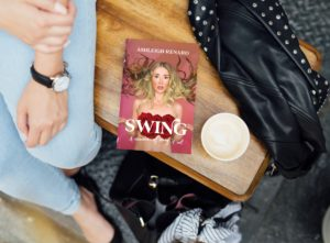 A brown wooden bench with denim-clad legs and a draped leather jacket, a book sits in the middle on the book cover is an unclothed woman with roses over her breasts and wild blond hair has a look on her face that says she greatly underestimated the complexities of her choices; her hands are palms facing up in a shrug, peach background, text at the top in white says Ashleigh Renard, white text SWING and A Memoir of Doing it All over the red roses