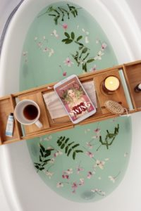 Glorious bathtub with flower clipping, bamboo tray lays across the edges of the tub, holds a coffee cup, a candle, and a tablet with a book cover showing an Unclothed woman with roses over her breasts and wild blond hair has a look on her face that says she greatly underestimated the complexities of her choices; her hands are palms facing up in a shrug, peach background, text at the top in white says Ashleigh Renard, white text SWING and A Memoir of Doing it All over the red roses
