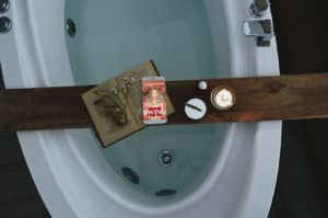 Bathtub with wooden tray displays candle, an antique print book, and a tablet with a book cover showing an Unclothed woman with roses over her breasts and wild blond hair has a look on her face that says she greatly underestimated the complexities of her choices; her hands are palms facing up in a shrug, peach background, text at the top in white says Ashleigh Renard, white text SWING and A Memoir of Doing it All over the red roses
